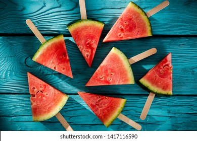 Fresh tasty watermelon on blue wooden board and summer time. Free space for your decoration and shadow of palm leaves.