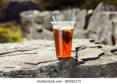 fresh tea in a disposable plastic cup with a spoon and a bag on a rock on the nature background