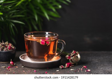 Fresh tea from rose petals in glass cup. Pink hot drink on dark brown background