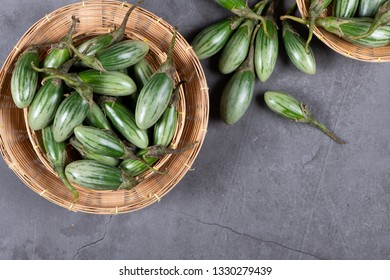 Fresh Thai green Eggplants on grey texture background with copy space, flat lay