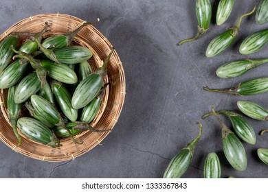 Fresh Thai green Eggplants on grey texture background, flat lay