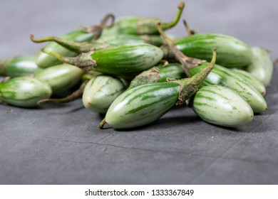 Fresh Thai green Eggplants on grey texture background with selective focus