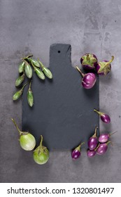 Fresh Thai green and purple Eggplants with chopping board on grey texture background, flat lay