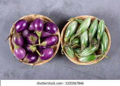 Fresh Thai green and purple Eggplants on grey texture background, flat lay