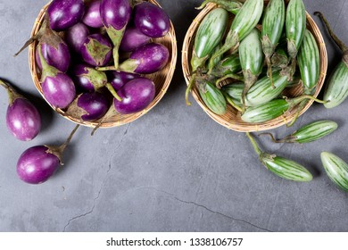 Fresh Thai green and purple Eggplants on grey texture background with copy space, flat lay