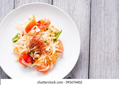 Fresh thai juicy Som Tam salad prepared with kohlrabi, carrot, wild garlic, tomato, cashew nuts and chili stripes. Traditional thai cuisine served on white plate.