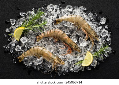 Fresh tiger shrimp on ice on a black stone table top view
