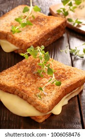 Fresh toast with cheese and herbs on wooden background