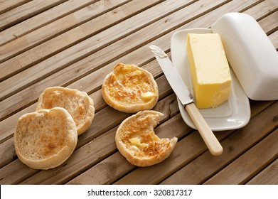 Fresh toasted hot English muffins, one with a bite missing, on a wooden slatted table with a pat of butter in a butter dish