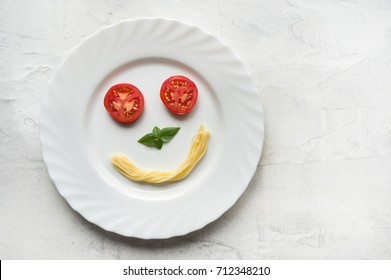 Fresh tomato, basil leaf and boiled spaghetti making smiley face. Funny food creative. Plate on concrete background. Top view.