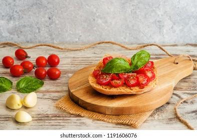 Fresh tomato bruschetta with basil, onion on rustic background.