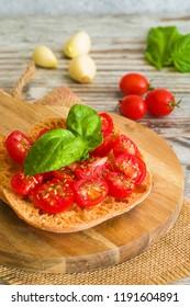 Fresh tomato bruschetta on wooden background. Italian food appetizer with fresh basil and garlic