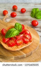 Fresh tomato bruschetta on wooden background. Italian food appetizer with fresh basil