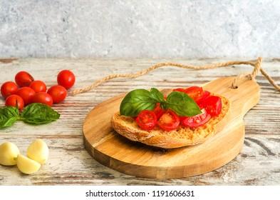 Fresh tomato bruschetta on wooden background. Italian food appetizer with fresh basil, and garlic