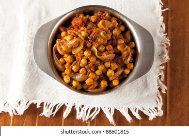Fresh tomato and chickpea curry in metal bowl shot from directly above.