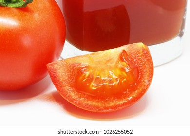 Fresh tomato and a glass of juice isolated on white background