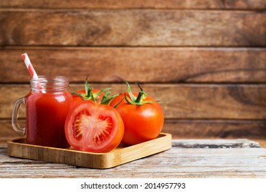 Fresh tomato juice in a glass with a cocktail tube with tomatoes  on a wooden table. Cutaway tomato. copy space - Shutterstock ID 2014957793