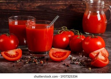 Fresh tomato juice in a glass with tomatoes salt and pepper on a dark background. Vegetable tomato drink for a healthy diet on a gray background. Top view.