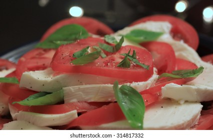 Fresh tomato and mozzarella layered with basil and olive oil drizzle in a romantic setting with red wine