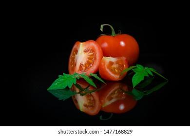 Fresh tomato on black background.