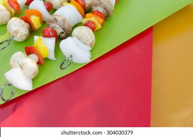 Fresh tomato, onion, mushroom and pepper kebabs on colorful mats with dappled lighting