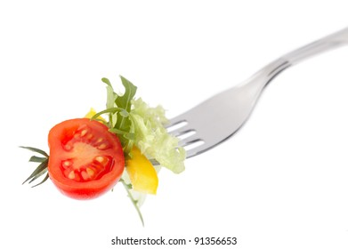 Fresh tomato and salad on a fork