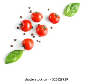 Fresh tomatoes and basil leaves on white background, top view