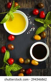 Fresh tomatoes, basil, olive oil and balsamic vinegar on wooden