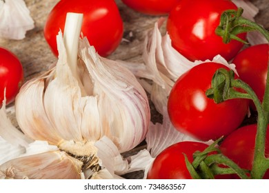 Fresh tomatoes and cloves of garlic on the wood