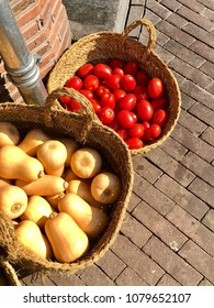 Fresh tomatoes and squash available for sale at a sidewalk market.