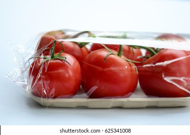 Fresh tomatoes wrapped in plastic packaging