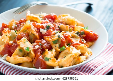 Fresh tortellini with homemade tomato sauce, chopped herbs and parmesan cheese