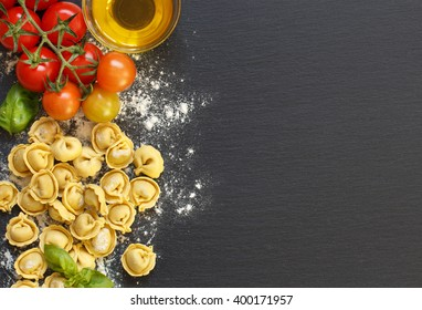 Fresh tortellini pasta and ingredients on a dark board top view