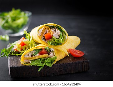 Fresh tortilla wraps with chicken and fresh vegetables on wooden board. Chicken burrito. Mexican cuisine. Copy space
