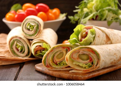 Fresh tortilla wraps with ham cheese and vegetables on wooden background