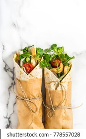 Fresh tortilla wraps on a marble pattern tabletop tied round with brown paper and string. Top view shot. Gourmet conception.