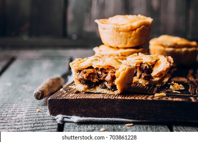 Fresh Traditional Australian meat mini pie on the wooden board on table background, closeup with copy space, rustic style. Delicious food