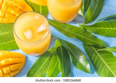 Fresh tropical fruit mango juice on blue woden background with mango fruit and leaves, refreshing and healthy drinks for summer.
