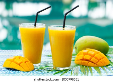 Fresh tropical fruit smoothie mango juice and fresh mango on a outdoor tropical background. Copy space.