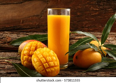Fresh tropical fruit smoothie mango juice  on wooden  background with leaves and fruits.