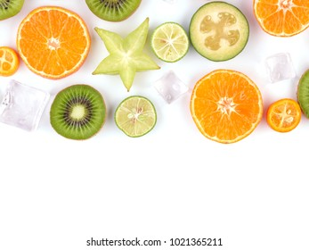 Fresh tropical slices of fruits isolated on white background. Juicy oranges, kiwis, carambolas and ice.