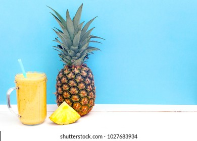 Fresh tropical smoothie and fresh pineapple on a turquoise background