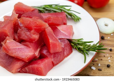 Fresh tuna fillet steaks with spices, vegetables and herbs on a plate. Preparing tuna for baking