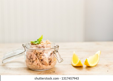 Fresh tuna in a glass mason jar with lemon slaces on a wooden table. Minimal style home made healthy food concept.