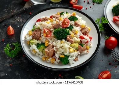 Fresh Tuna rice salad with sweet corn, cherry tomatoes, broccoli, parsley and lime in black bowl
