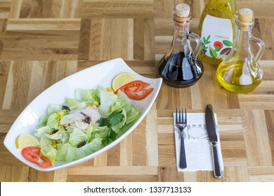 Fresh tuna salad with lettuce, sweet corn, onion, black olives and salad dressing on a wooden table