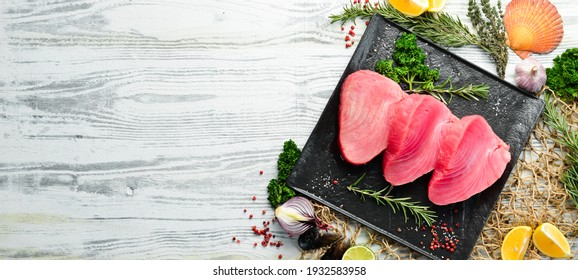 Fresh tuna steak on a black stone plate. On a white wooden background. Top view.