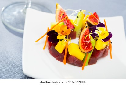 Fresh tuna tartare formed as wreath with ripe figs, cucumber, julienne carrot and pansies flowers on plate