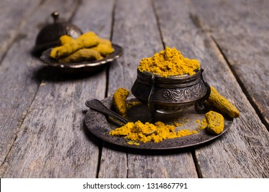 Fresh turmeric root and powder. Healthy seasoning ingredient for vegan cuisine. Dark rustic wooden background. Selective focus.