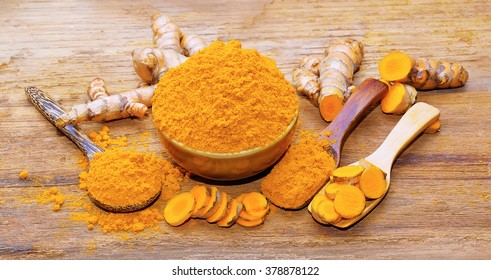 fresh turmeric roots on wooden table